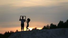 Silhouettes des paires romantiques espiègles drôles tenant le cadre vide et l'embrassant sur le fond du ciel de coucher du soleil banque de vidéos