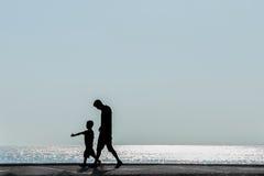 Silhouettes des parents avec le bébé sur le fond de mer Photographie stock libre de droits
