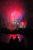 Silhouettes des personnes au port par des feux d'artifice Photographie stock