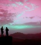 Silhouettes des personnes avec le ciel étranger Photos libres de droits