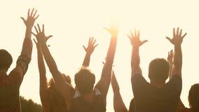 Silhouettes des personnes avec les mains augmentées au coucher du soleil banque de vidéos