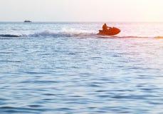 Silhouettes des personnes dans le mouvement sur le scooter de mer photographie stock libre de droits