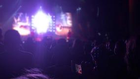 Silhouettes des personnes dans les lumières lumineuses d'un concert 4K banque de vidéos