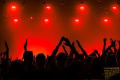 Silhouettes des personnes dans un lumineux dans le concert de rock de bruit devant l'étape Mains avec des klaxons de geste Cela b Images stock
