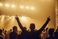 Silhouettes des personnes dans un lumineux dans le concert de rock de bruit devant l'étape Mains avec des klaxons de geste Cela b Photographie stock libre de droits