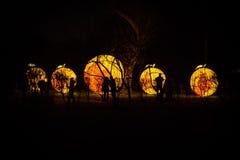 Silhouettes des personnes devant l'installation orange de lanternes Image libre de droits