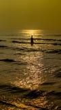 Silhouettes des personnes en mer Images stock