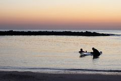 Silhouettes des personnes en mer dans le coucher du soleil photos stock