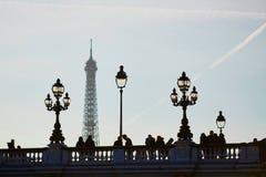 Silhouettes des personnes et des lanternes sur le pont célèbre d'Alexandre III et le Tour Eiffel Photo libre de droits