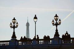 Silhouettes des personnes et des lanternes sur le pont célèbre d'Alexandre III et le Tour Eiffel Photos stock