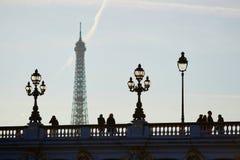 Silhouettes des personnes et des lanternes sur le pont célèbre d'Alexandre III et le Tour Eiffel Images stock