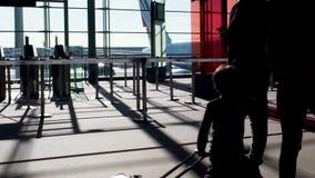 Silhouettes des personnes marchant à travers le terminal ensoleillé, voyage par avion, mouvement lent clips vidéos