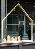 Silhouettes des personnes marchant devant des immobiliers de location Photographie stock libre de droits