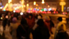 Silhouettes des personnes marchant le long d'une rue passante, dans le defocus, vie nocturne de la ville banque de vidéos
