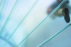 Silhouettes des personnes marchant sur un escalier en spirale en verre Photo libre de droits