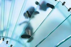 Silhouettes des personnes marchant sur un escalier en spirale en verre Photographie stock libre de droits