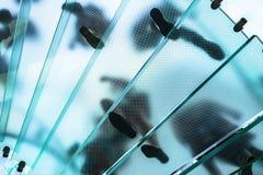 Silhouettes des personnes marchant sur un escalier en spirale en verre Images libres de droits