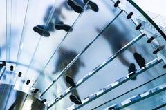 Silhouettes des personnes marchant sur un escalier en spirale en verre Images stock