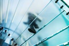 Silhouettes des personnes marchant sur un escalier en spirale en verre Photographie stock