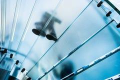 Silhouettes des personnes marchant sur un escalier en spirale en verre Image libre de droits