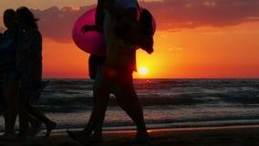 Silhouettes des personnes marchant vers le soleil sur une belle plage de coucher du soleil UHD clips vidéos