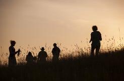 Silhouettes des personnes sélectionnant des fleurs pendant le soltice de milieu de l'été Photographie stock libre de droits