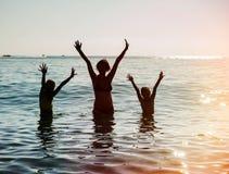 Silhouettes des personnes sautant en mer Photographie stock