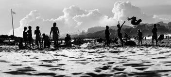 Silhouettes des personnes sur la plage ayant un temps d'amusement des vacances Image stock