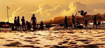 Silhouettes des personnes sur la plage ayant un temps d'amusement des vacances Image libre de droits