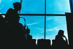 Silhouettes des personnes sur le fond d'une fenêtre dans la salle d'attente à l'airpor Images libres de droits