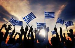 Silhouettes des personnes tenant le drapeau de la Grèce Photographie stock libre de droits