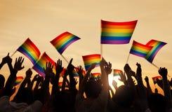 Silhouettes des personnes tenant le drapeau gai de Pride Symbol Photographie stock libre de droits