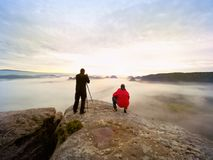 Silhouettes des photographes de l'homme Hommes sur la montagne, deux hommes prenant des photos dans le lever de soleil de matin d Image libre de droits
