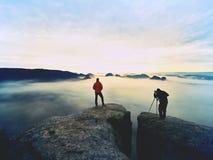 Silhouettes des photographes de l'homme Hommes sur la montagne, deux hommes prenant des photos dans le lever de soleil de matin d Photographie stock libre de droits