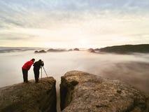Silhouettes des photographes de l'homme Hommes sur la montagne, deux hommes prenant des photos dans le lever de soleil de matin d Photos stock