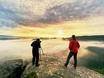 Silhouettes des photographes de l'homme Hommes sur la montagne, deux hommes prenant des photos dans le lever de soleil de matin d Images stock