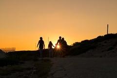 Silhouettes des randonneurs appréciant le coucher du soleil Photo stock