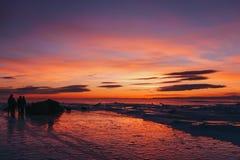 Silhouettes des touristes contre un beau coucher du soleil sur le lac Baïkal en hiver photo stock