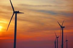 Silhouettes des turbines de vent à une ferme de vent au coucher du soleil Photo libre de droits