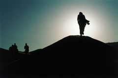 Silhouettes in the Desert. Silhouettes of people in the late afternoon sun, walking across the hills of the desert in Namibia, Africa Stock Photos
