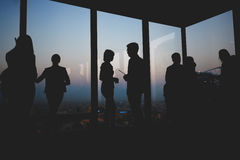 Silhouettes of different groups of businesspeople talking with each other in skyscraper office interior, Stock Images
