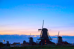 Silhouettes of Dutch mills near the lake at sunset Stock Images