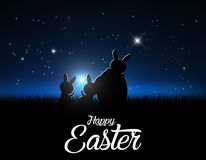 Silhouettes of easter bunnies against a moonlight and stars.  Royalty Free Stock Images