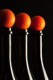 Silhouettes of elegant wine bottles with golf balls Stock Images