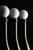 Silhouettes of elegant wine bottles with golf balls Stock Photography