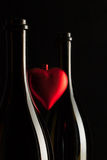 Silhouettes of elegant wine bottles with red heart Royalty Free Stock Photo