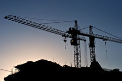Silhouettes of elevating cranes Stock Images