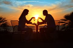 silhouettes för par s sitter solnedgångtabellen Royaltyfri Foto