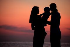 Silhouettes of family on hands against sea decline. Silhouettes of parents with child on hands against sea decline stock photos