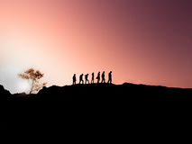 Silhouettes of a family of  walking  at sunset. Silhouettes of a group of people walking  at sunset Royalty Free Stock Images